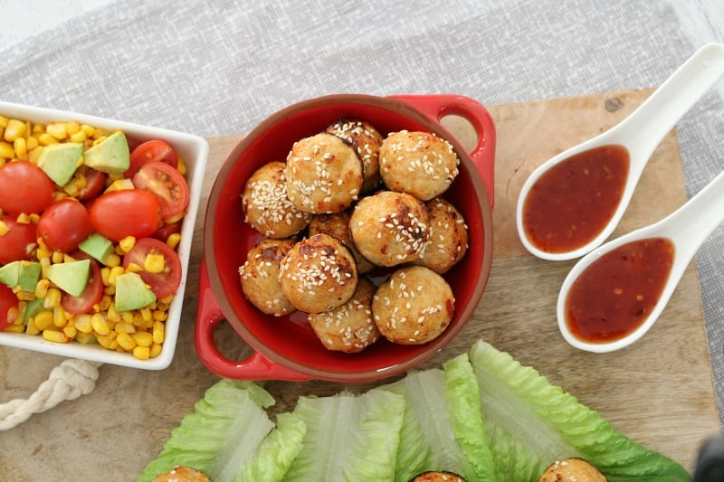 An overhead shot of meatballs in a dish, with cos lettuce leaves, corn kernels, chopped tomatoes and dipping sauce on a board