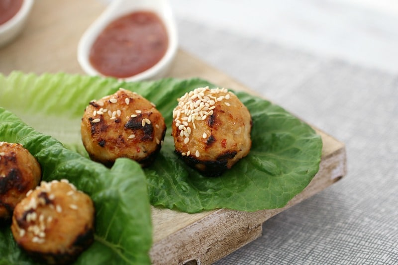 A close up of meatballs sprinkled with sesame seeds on cos lettuce leaves and dipping sauce in a spoon nearby