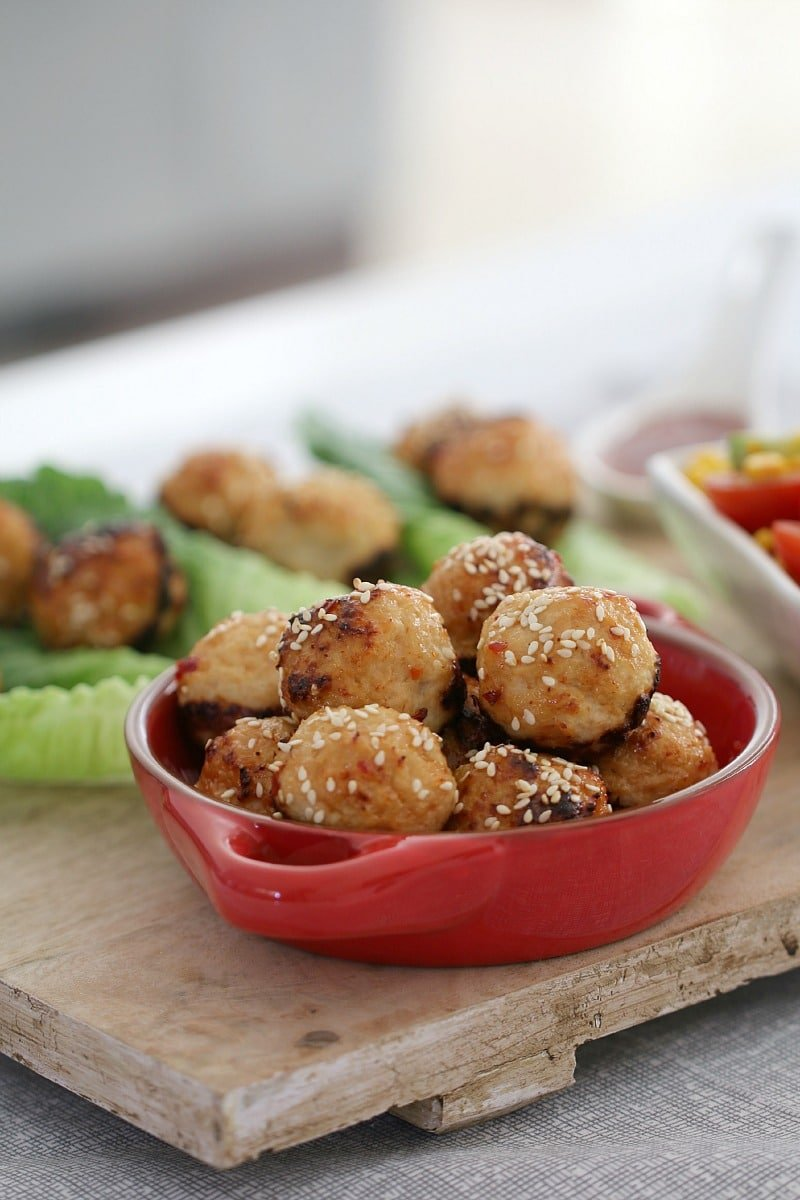 A bowl of Thai Chicken Meatballs in a small red dish, with meatballs on cos lettuce leaves in the background