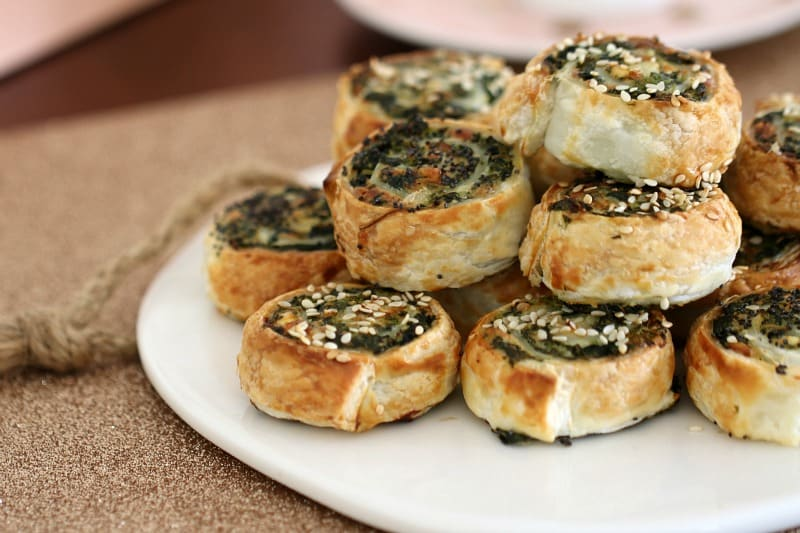Baked pinwheel scrolls filled with spinach and feta, and piled on a serving dish