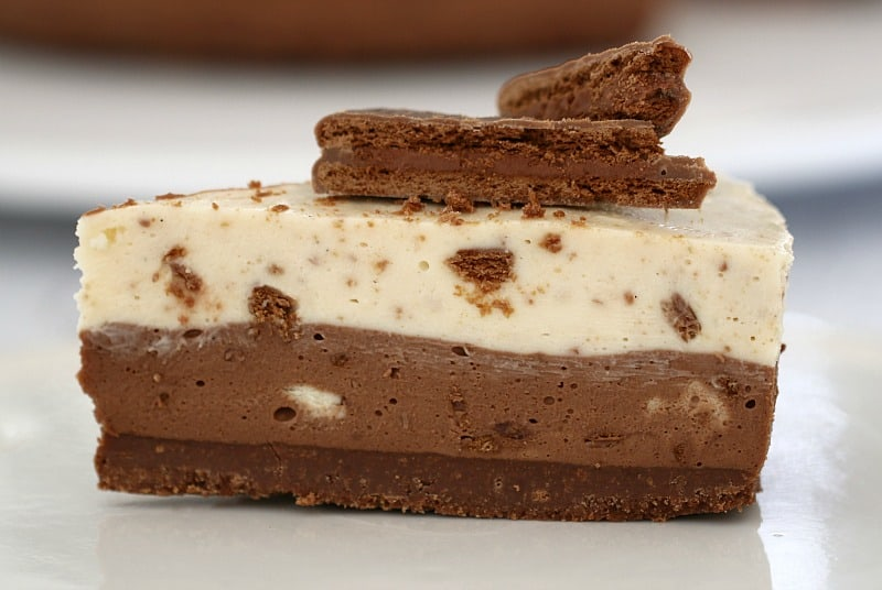 A side view of a serve of cheesecake, with a chocolate biscuit base, a chocolate layer and a creamy layer on top, then decorated with chopped Tim Tam biscuits