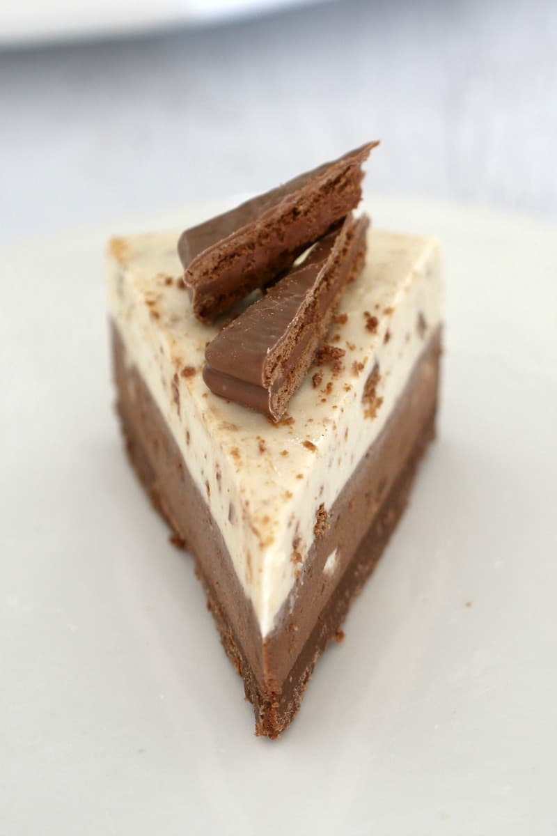 A portion of no-bake Tim Tam cheesecake with wedges of Tim Tam biscuits on top