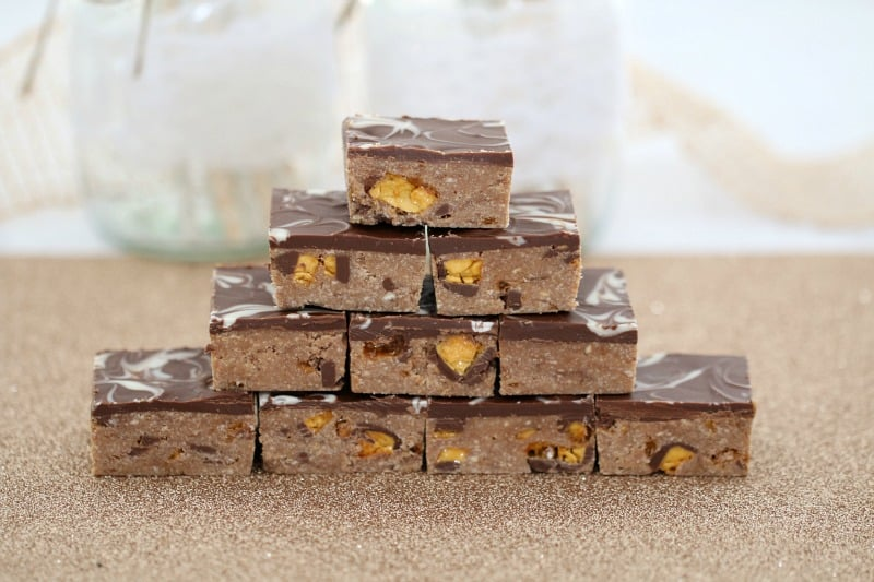 A stack of pieces of chocolate honeycomb slice on a bench