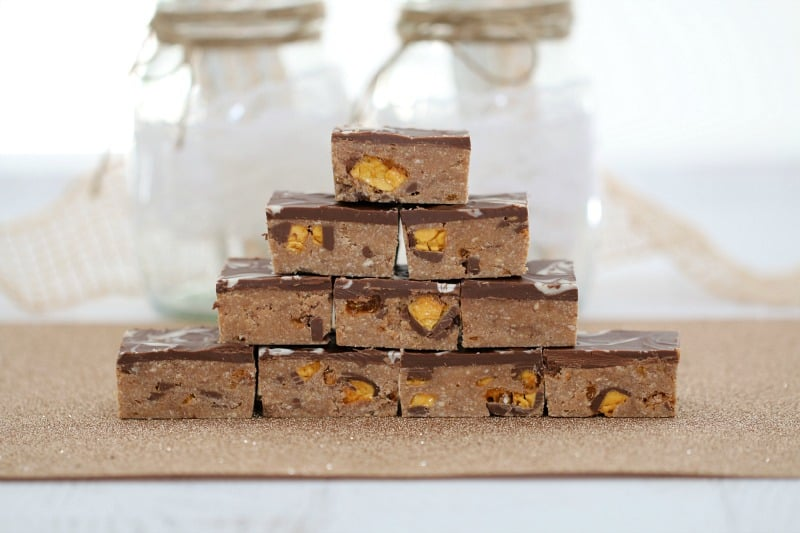 A side view of a stack of chocolate honeycomb slice pieces, showing chunks of honeycomb inside