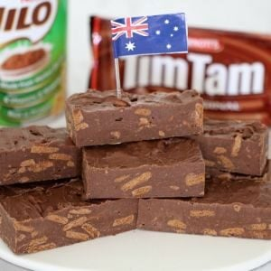 A stack of fudge with an Australian flag in front of a tin of Milo and packet of Tim Tams biscuits