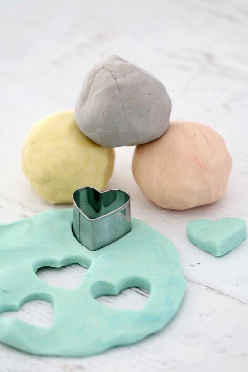 Yellow, purple, pink and green pastel playdough with a metal love heart shaped cutter.