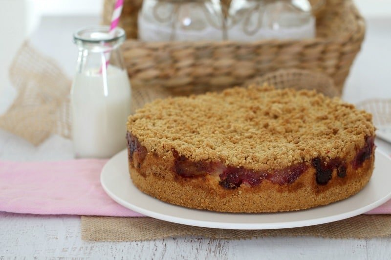 A cake made with a crumble topping in front of a basket and a small bottle filled with cream