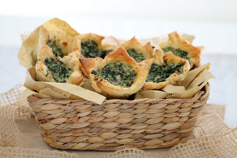 A basket piled with golden pastry spinach and ricotta tarts