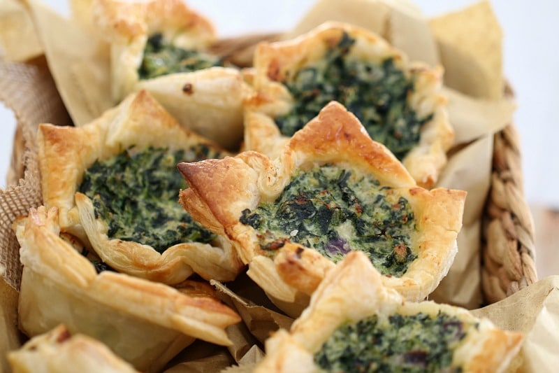 A close up of spinach and ricotta tarts in golden puff pastry squares