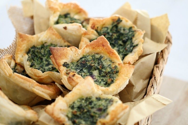 Spinach and ricotta tarts in golden puff pastry piled in a basket