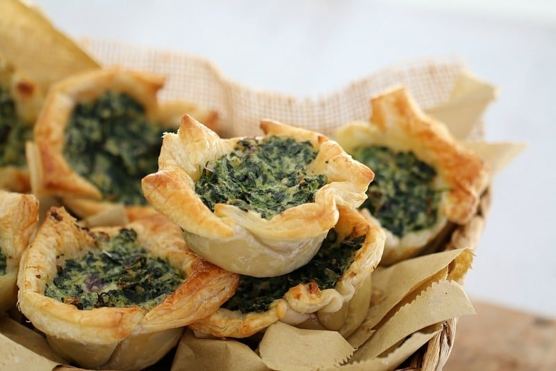 Puff pastry squares filled with spinach and ricotta piled in a basket