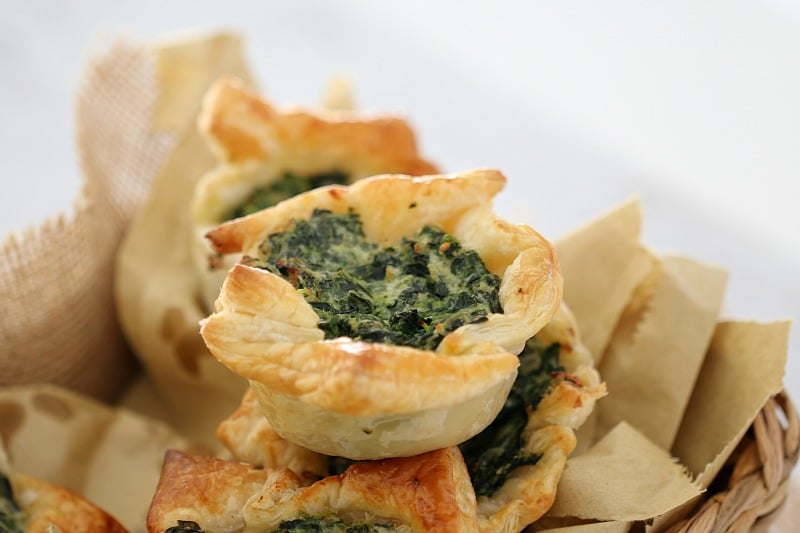 A pile of puff pastry squares filled with spinach and ricotta