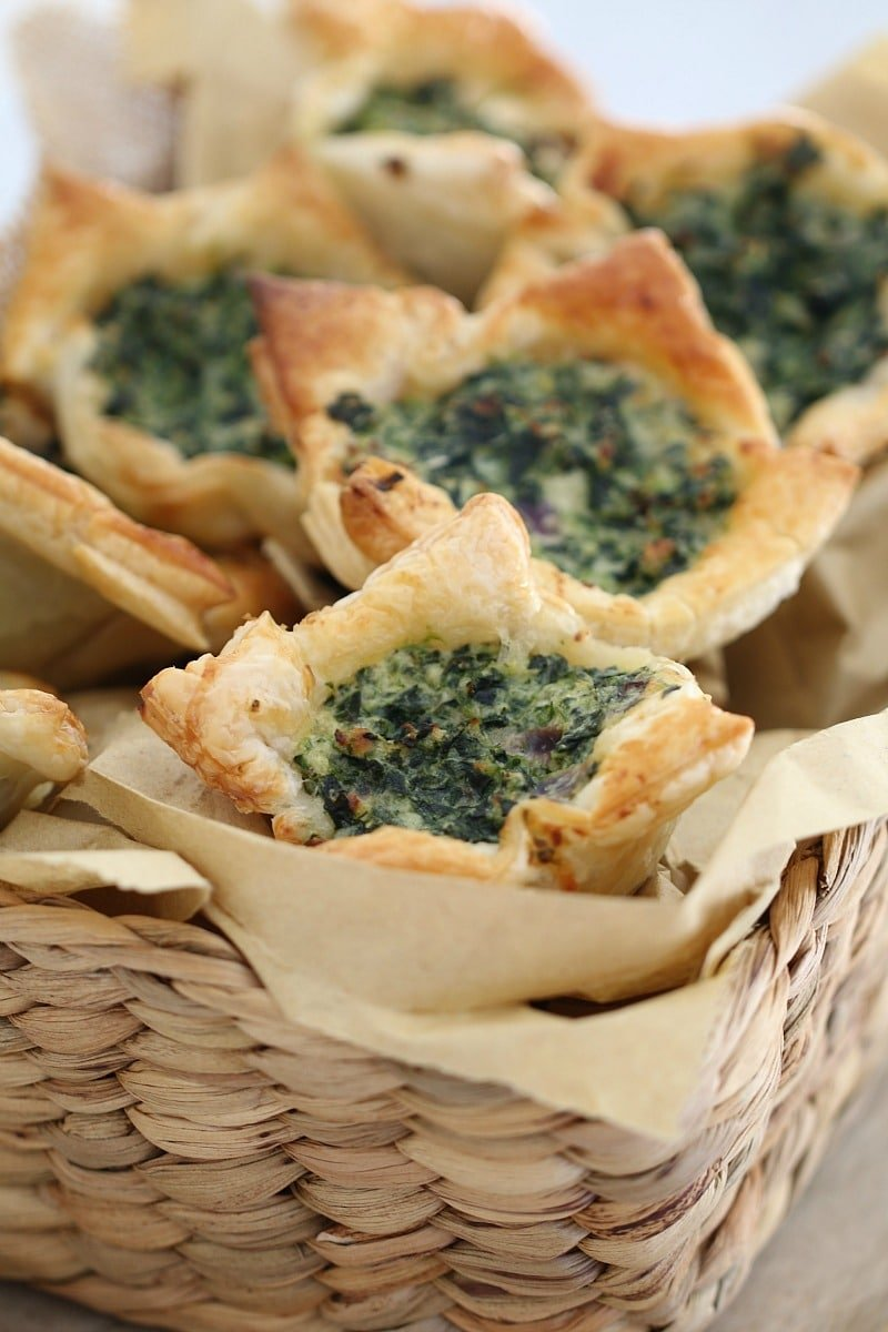 A close up of puff pastry squares with a spinach and ricotta filling  in a basket