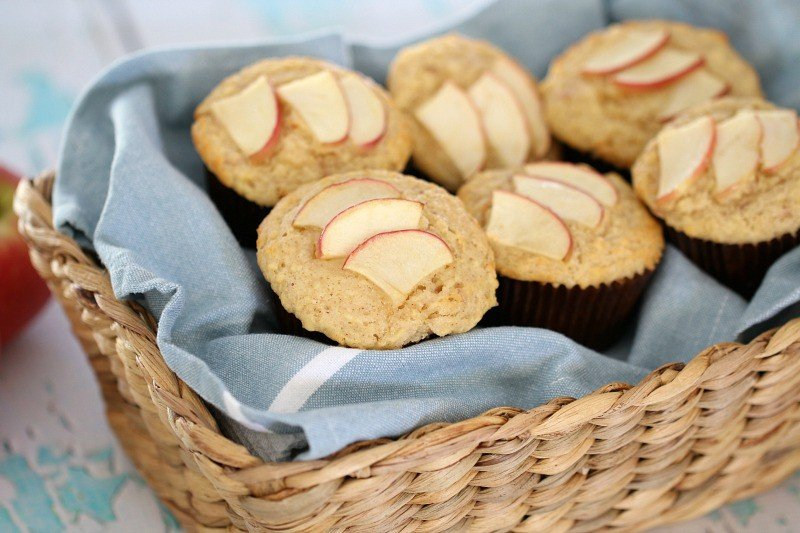 A cane basket with a tea towel and muffins inside