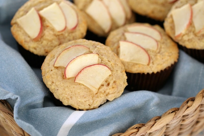 Muffins topped with sliced apple piled in a cane basket