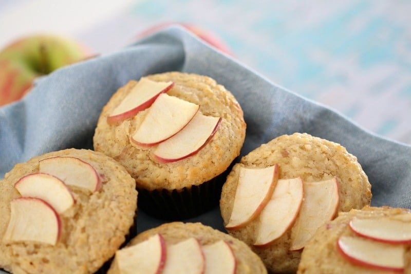Muffins with slices of apple on top in a basket