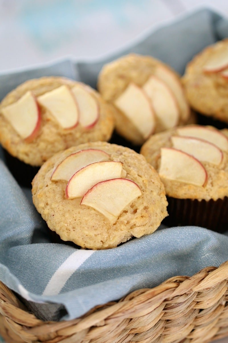 A basket full of apple topped muffins on a blue tea towel