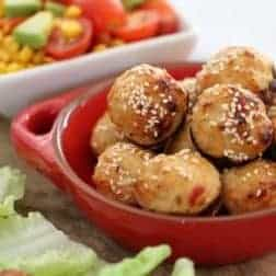 Round meatballs sprinkled with sesame seeds piled in a small red dish