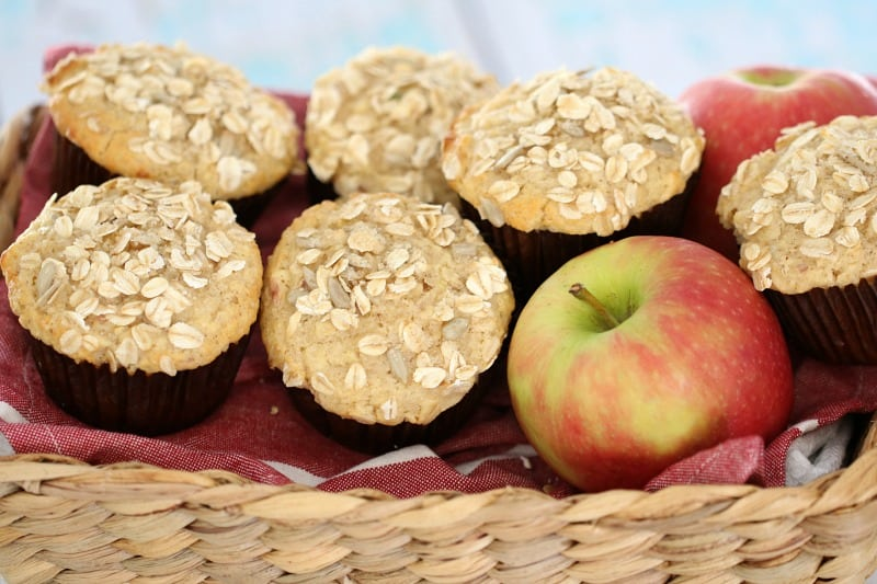 Oat topped muffins piled in a basket with an apple