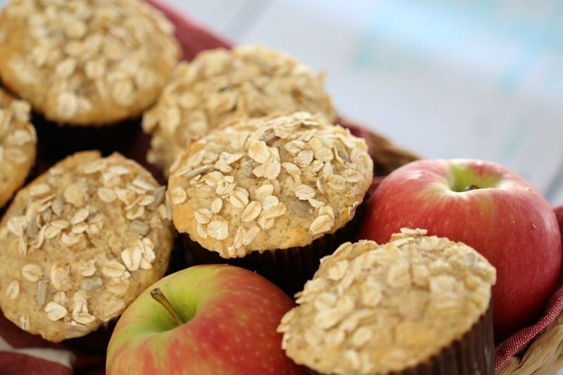 A close up of apples and muffins with oats on top in a basket