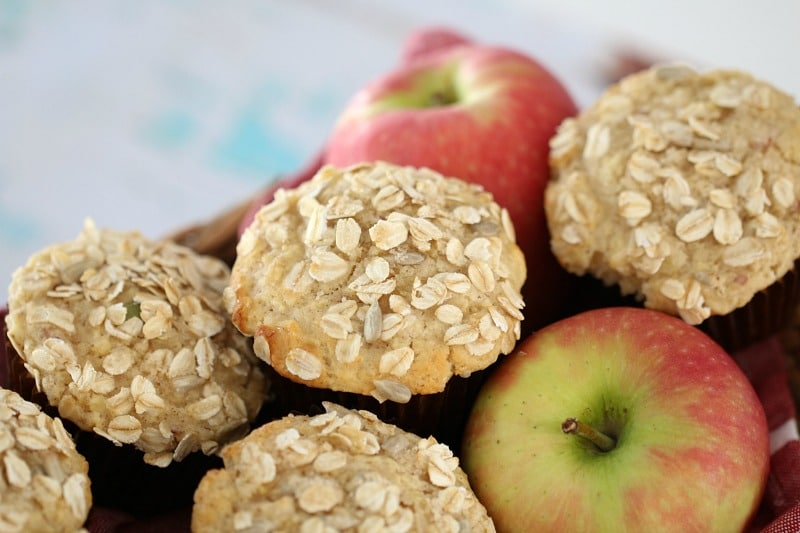 A pile of red apples and muffins sprinkled with oats