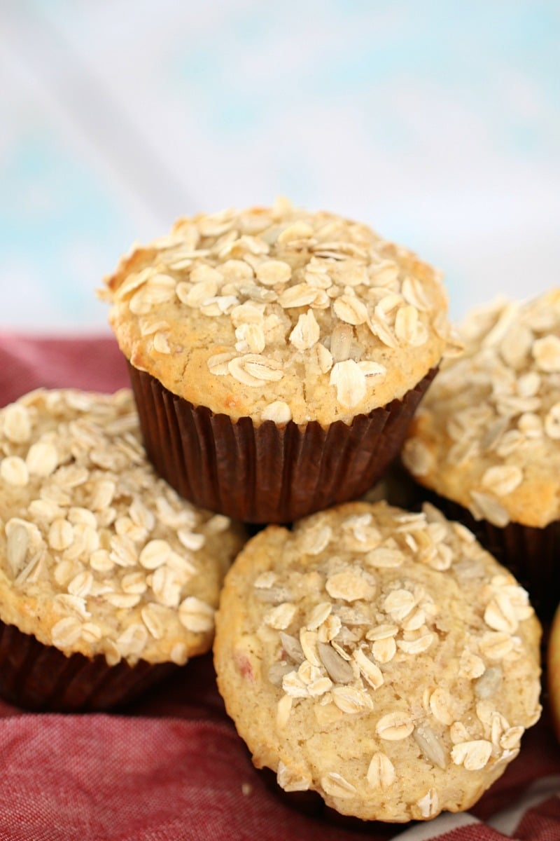 A close up of a pile of muffins in muffin cases with oats sprinkled over the tops