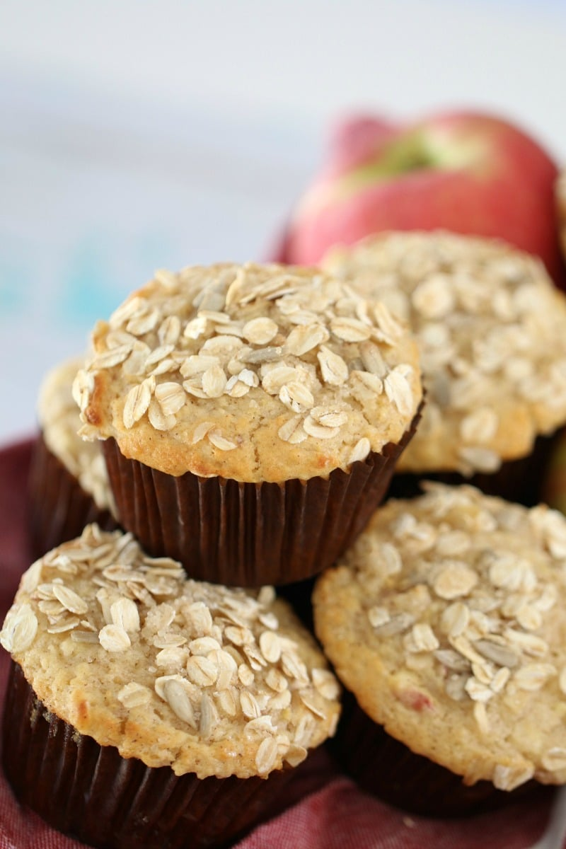 A pile of muffins in brown muffin cases with oats sprinkled over the tops