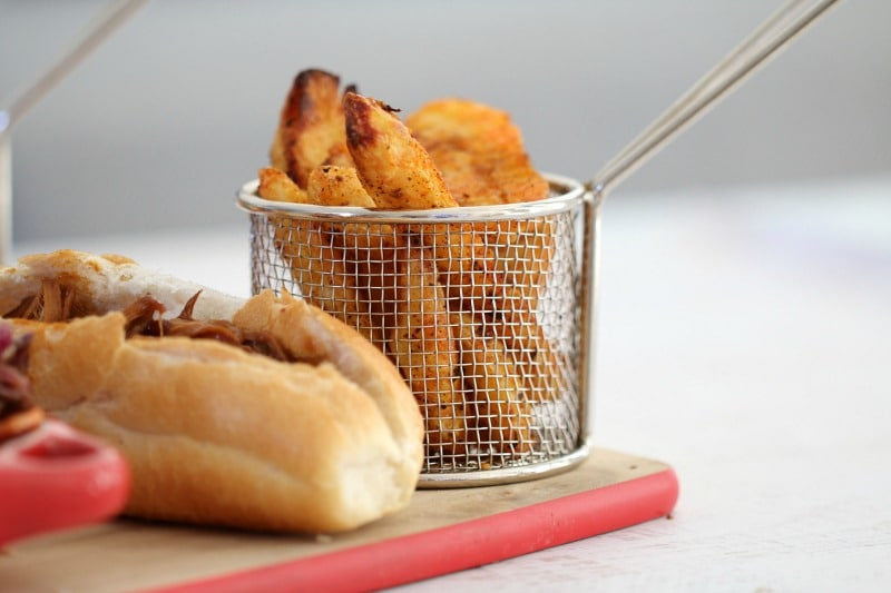 Crispy potato wedges in a little wire basket and a hot-dog roll on a wooden board