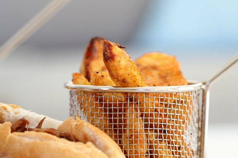 Crispy potato wedges stacked in a small wire basket