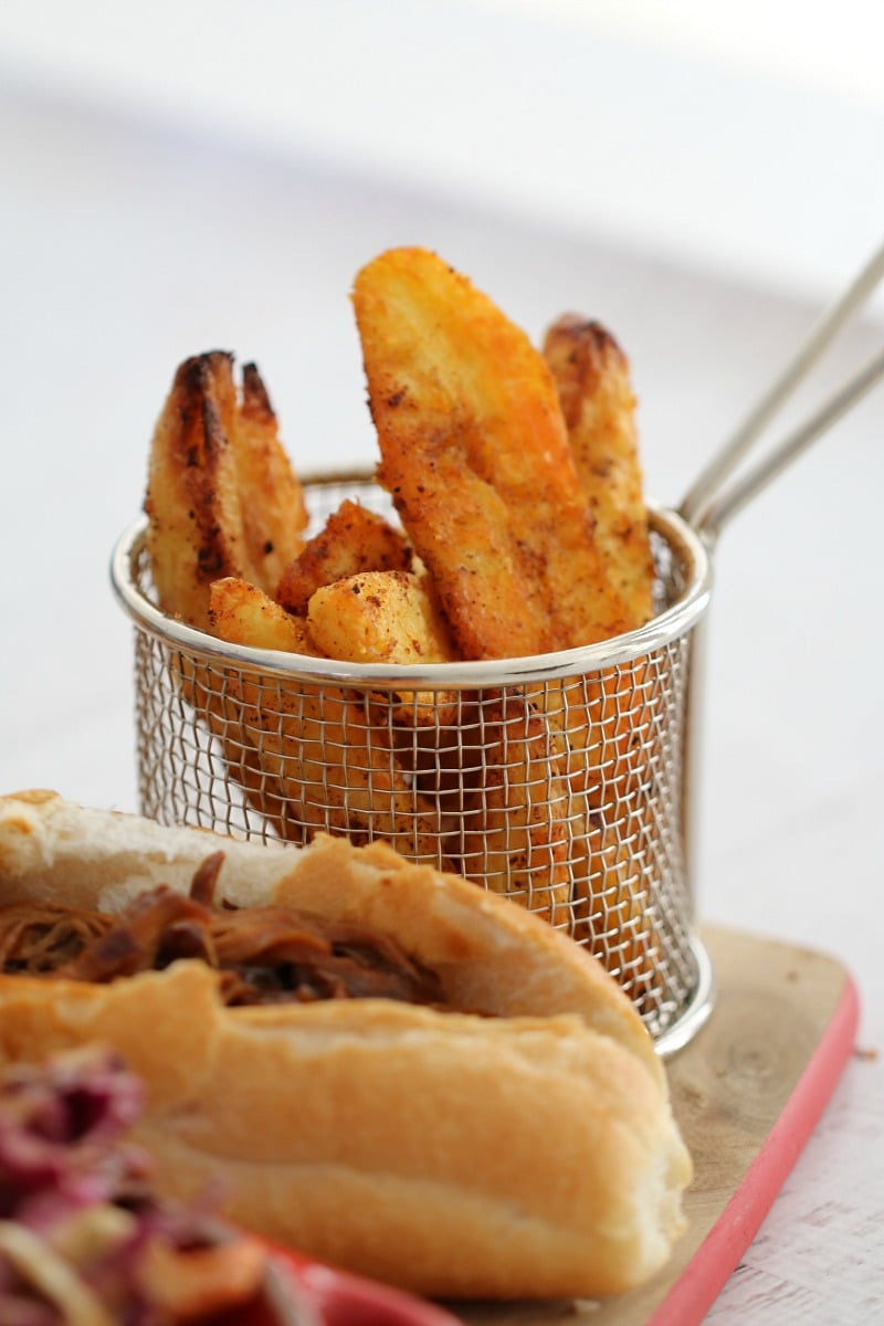 A hot-dog roll filled with meat and a small wire basket stacked with crispy potato wedges on a wooden board