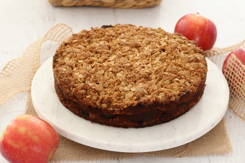 A streusel cake with apples in the background.