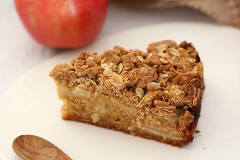A piece of teacake with apple in the middle and crumble on the top.