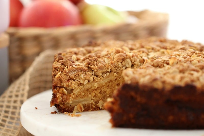 A cake layered with apple slices and crumble topping with a slice taken out.