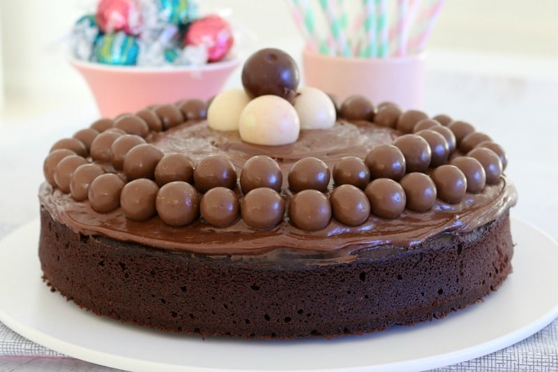 A close up of Maltesers and Lindt balls on top of a chocolate cake covered with chocolate ganache