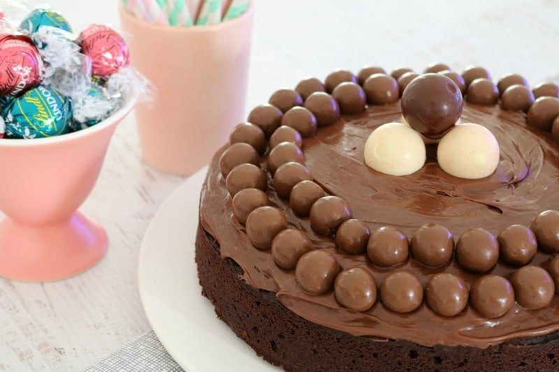 A close up of Maltesers and Lindt balls and chocolate ganache on top of a chocolate cake