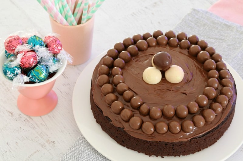 An overhead shot of a round chocolate cake covered with chocolate ganache, Maltesers and Lindt balls.