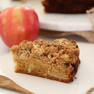 A slice of Apple Crumble cake on a white plate in front of an apple.