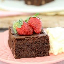 A square of chocolate brownie served on a plate with two fresh strawberries on top and a dollop of cream beside