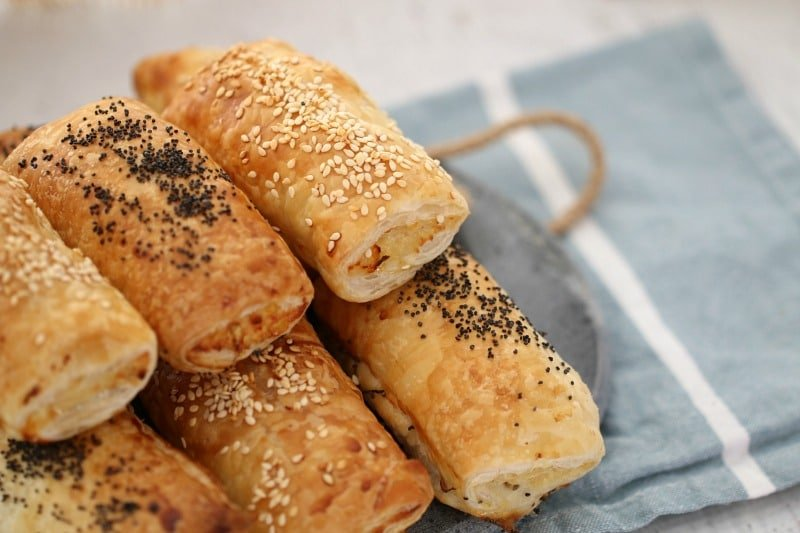 A stack of golden baked sausage rolls, some sprinkled with sesame seeds and some sprinkled with poppy seeds