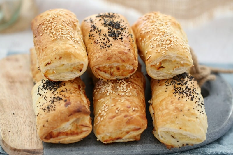 Baked sausage rolls sprinkled with sesame seeds and poppy seeds