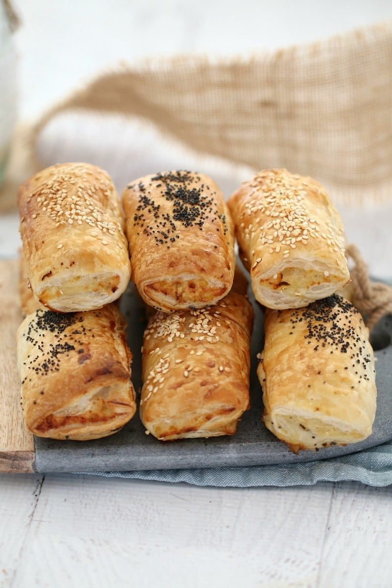 Six sausage rolls stacked on a wooden and marble board