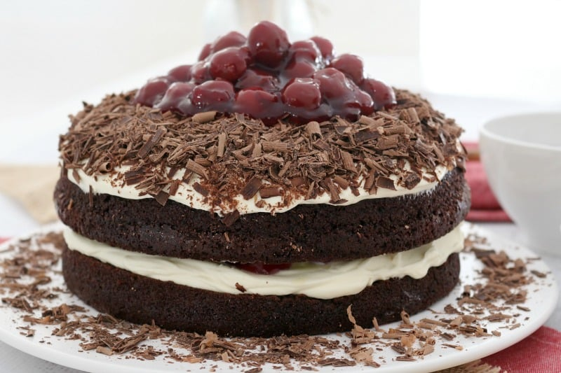 Two layers of chocolate cake sandwiched together and topped with whipped cream, grated chocolate and morello cherries on top