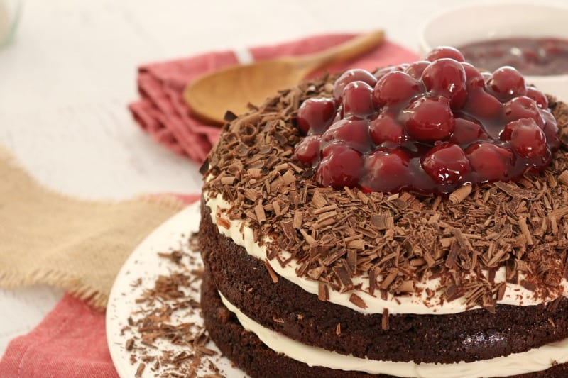 Grated chocolate around the edge of a layered whipped cream and chocolate cake, with cream, grated chocolate and morello cherries on top
