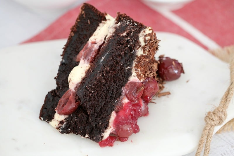A serve of cake made with two chocolate layers sandwiched together, and topped with whipped cream, grated chocolate and morello cherries