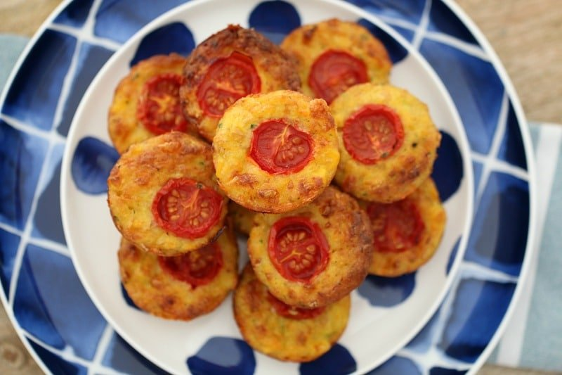 Looking down on a plate of a dozen mini quiche bites, each with a slice of tomato on top
