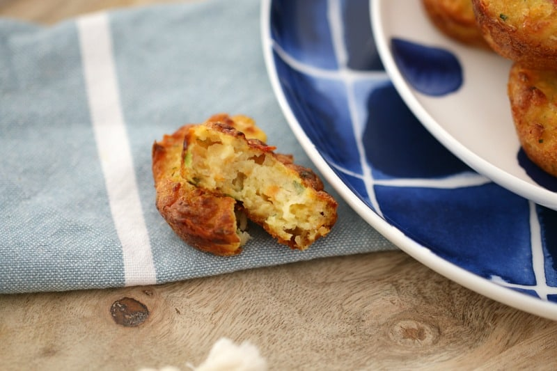 A mini vegetable and ham muffin split open and placed on a tea towel next to a blue plate