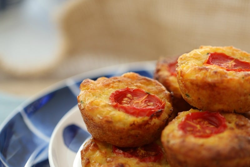 A side view of a pile of mini quiche bites, each with a slice of cherry tomato on top