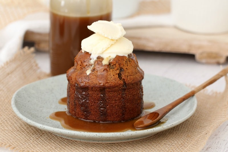 A bottle of caramel sauce behind an individual sticky date pudding with caramel sauce and whipped cream to serve.