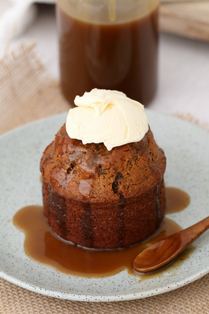 An individual sticky date pudding on a plate with caramel sauce poured over and whipped cream on top