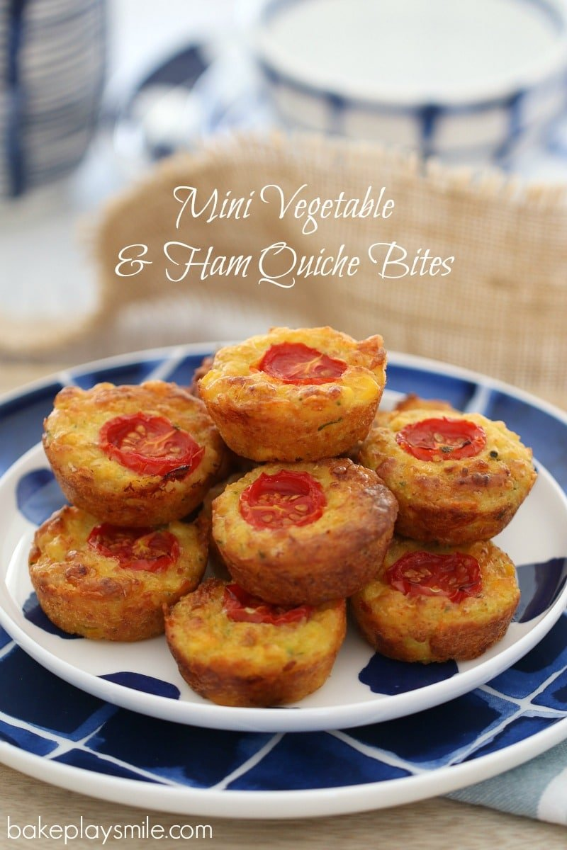 A plate of mini quiche bites each with a slice of tomato on top, and served on a blue and white plate